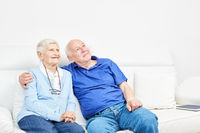 Glückliches altes Ehepaar auf dem Sofa