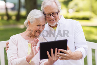 senior couple with video chat on tablet pc at park