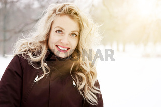 blond woman in winter landscape with sun flare