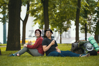 Young couple - man and woman - tourists with backpacks are eating the icecream in the park