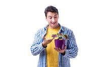 Young man with flower pot isolated on white