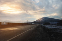 A country asphalt road illuminated by the rays of the sun through the clouds leading to the mountain on which the rays of the sun fall in the evening