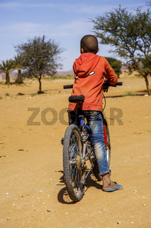 Tinzouline, Morocco - February 26, 2016: Rear view of Moroccan boy riding bicycle in desert in Tinzouline village in Morocco