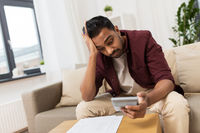 confused man with papers and calculator at home