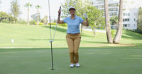 Woman golfer cheering as she sinks her putt