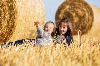 Happy mother and two year old girl next to hay bales in harvested field