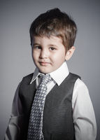 first employment, little businessman, brown-haired boy dressed in suit and tie with faces and funny expressions