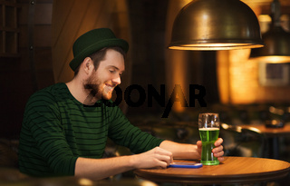 man with smartphone and green beer at bar or pub