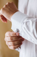 the man corrects cuff links on a shirt. the groom puts on on a wedding. men's cuff links on a white shirt close up.