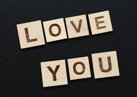Words LOVE YOU on wooden signs over black