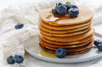 Stack of pancakes with honey and blueberry.