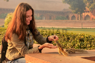 Young woman feeding Indian palm squirrels at Agra Fort, Uttar Pradesh, India