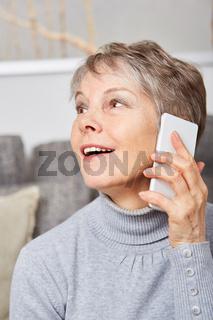 Seniorin mit Smartphone blickt überrascht