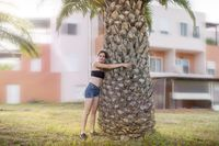 young smiling woman is hugging a palm tree