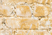 Close-up Textured background of a multi-colored brick painted in yellow. A sizzling yellow paint on an old broken brick. Grunge style