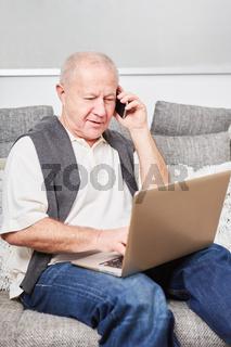 Senior mit Laptop und Smartphone