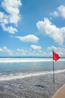 a beach at Bali with a red flag