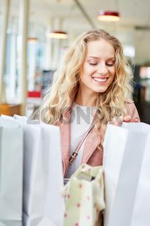 Kundin schaut in ihre Einkaufstüten
