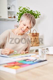 Alte Frau mit Demenz beim kreativen Malen