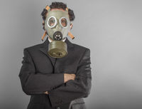 portrait of a business man with gas mask over grey background