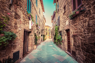 Narrow street in an old Italian town of Pienza. Tuscany, Italy. Vintage