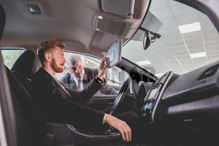 Young man choosing new generation electro car.