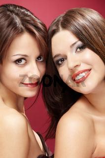 Two beautiful girlfriends smile