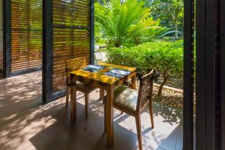 restaurant table set overlooking tropical garden