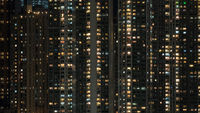 Window lights in high-rise apartment block at night