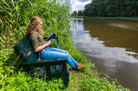 Dutch woman reading book on bench at water