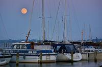 Segelboote und Motoryachten im Yachthafen zur blauen Stunde bei Vollmond