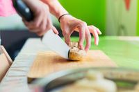 Female hands cut into large wooden mushrooms on a cutting board.