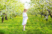 Pregnant woman wearing big hat and white dress in blooming garden