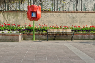 Tulip shaped public phone and wooden bench in front of built-in tulip flower box and grunge wall on tiled stone floor