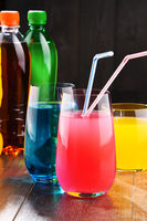 Glasses and bottles of assorted carbonated soft drinks in variety of colors