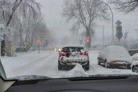 Ein PKW steht im Schneegestöber vor geschlossenen Bahnschranken.