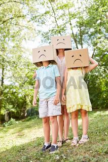 Familie mit Kindern im Garten unter Pappkartons
