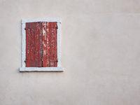 Fenster mit rotem Fensterladen in einem hell gestrichenen Haus