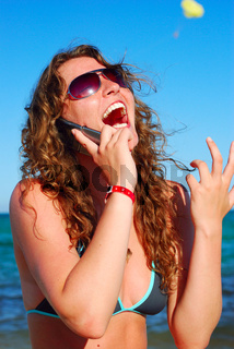 cheerful woman is talking phone near sea