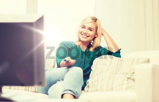 smiling woman with remote watching tv at home