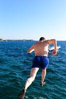 Mann hüpft ins Meer