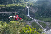 Cascades route, Banos, Ecuador - November 28, 2017: Tourists gliding on the zip line trip against Bridal veil (Manto de la novia), waterfall
