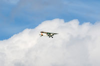 Small engine airplane flying among the clouds