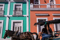 Horse pulling carriage in front of colorful colonial facade