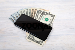 cellular phone and American dollar money on white