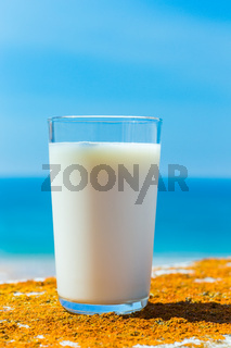 Glass filled with cow milk sea and sky