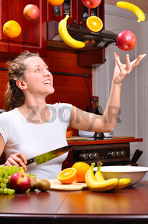 happy woman is cooking fruit salad out of flying fruits
