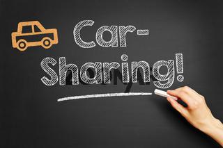 Hand schreibt Car-Sharing an Tafel