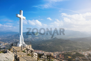 A white cross over Jaen town at the mountain, a symbol of the town with Sierra Magina mountains on background on sunny day, Andalusia region, Spain.