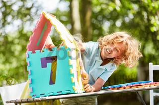 Junge baut aus Puzzleteilen ein Miniatur Haus